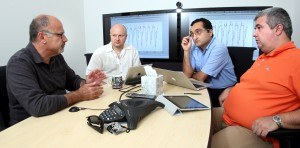 Habib Najm, Bert Debusschere, Khachik Sargsyan, and Cosmin Safta compare observational data with climate land model simulation results in a weekly meeting for the ACME UQ project. (Photo by Dino Vournas)