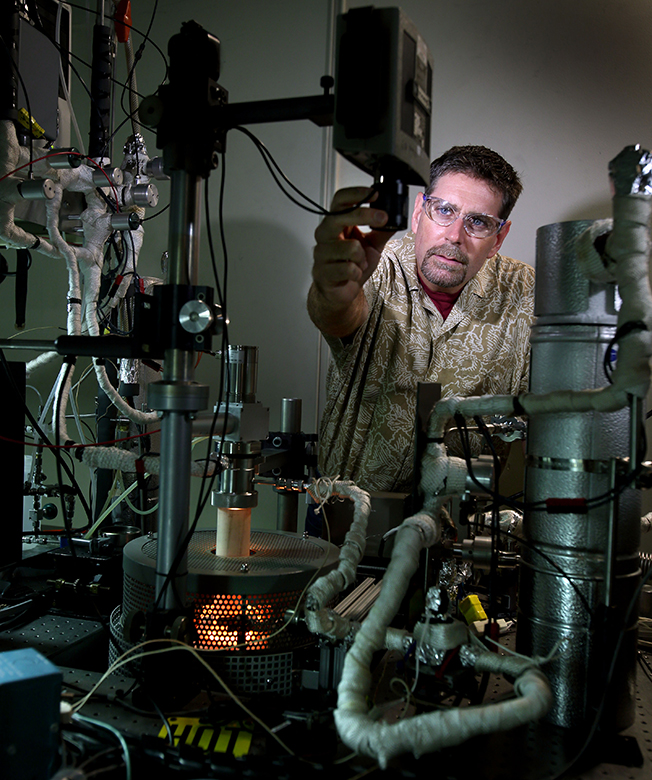 Tony McDaniel carefully adjusts the setting on an optical pyrometer used to measure the temperature of the metal-oxide particles undergoing reduction. Incandescence from the experimental reactor can be seen in the foreground and attests to the extreme temperature used to extract oxygen from the metal-oxide particles. (Photo by Dino Vournas)