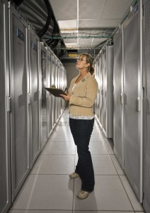 Kathye Chavez inspects a component board in one of the many cabinets that make up Sandia's Red Sky.